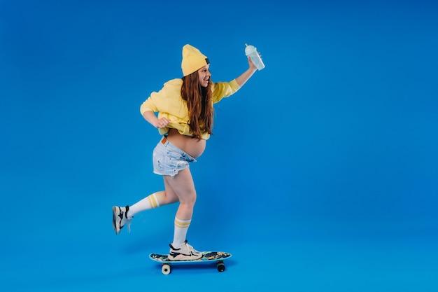 Una ragazza incinta in abiti gialli con un bicchiere di succo cavalca uno skateboard su uno sfondo blu