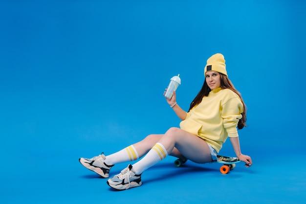 Una ragazza incinta in abiti gialli con un bicchiere di succo si siede su uno skateboard su uno sfondo blu