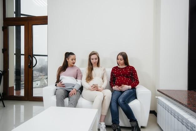 Le ragazze incinte si siedono sul divano e si divertono a chiacchierare tra loro. gravidanza e cura del futuro del bambino.