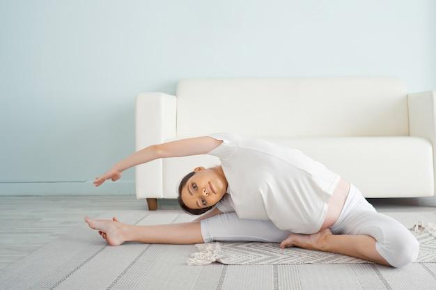 La signora incinta fa janu sirsasana seduta sul pavimento a casa