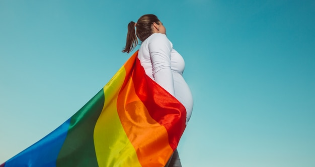 Donna lesbica incinta con un orgoglio gay, bandiera arcobaleno, sfondi lgbtq con spazio di copia extra, gravidanza