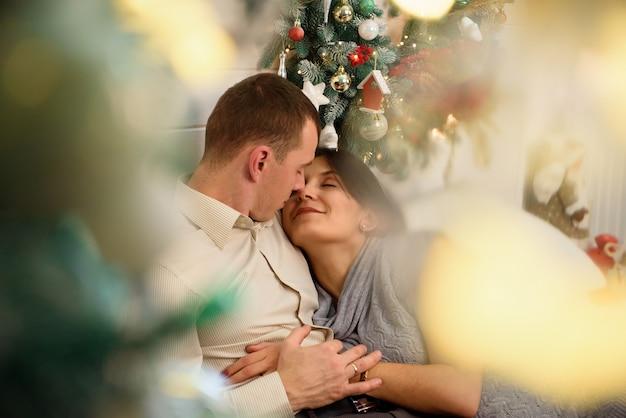 Madre incinta e suo marito a casa con decorazioni natalizie.
