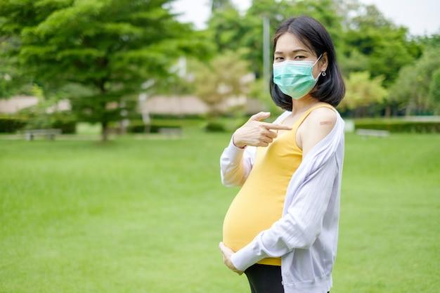 Una madre incinta che indossa abiti casual viola e gialli mostra un cerotto sulla parte superiore del braccio