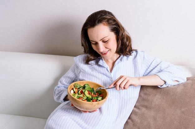 Donna sorridente incinta in camicia blu che si siede sul sofà che mangia insalata di verdure sana
