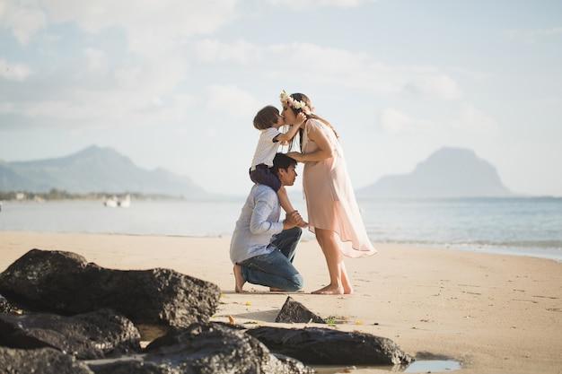 Donna incinta, bambino e uomo di razza mista sulla spiaggia