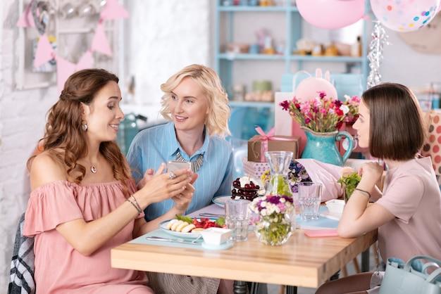 Gestante. bella donna incinta che indossa un abito rosa chiaro incontrando i suoi amici con baby shower