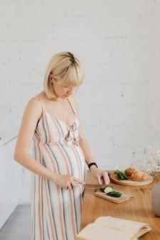 Donna incinta che cucina in una cucina