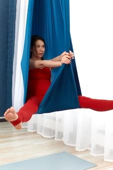 Donna incinta che fa esercizi su un'amaca ad aria, yoga antigravità, rafforzamento della salute della mamma e del futuro bambino, concetto di allenamento durante la gravidanza.