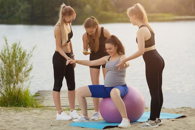 Donna incinta che fa esercizi di fitness con una palla con un allenatore e amici