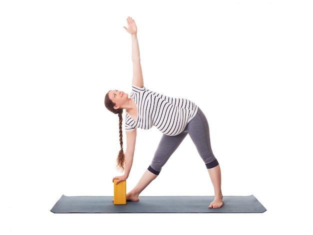 Donna incinta che fa yoga asana utthita trikonasana