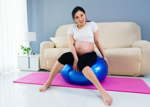 Donna incinta che fa esercizio di yoga sulla palla fitness nel soggiorno di casa