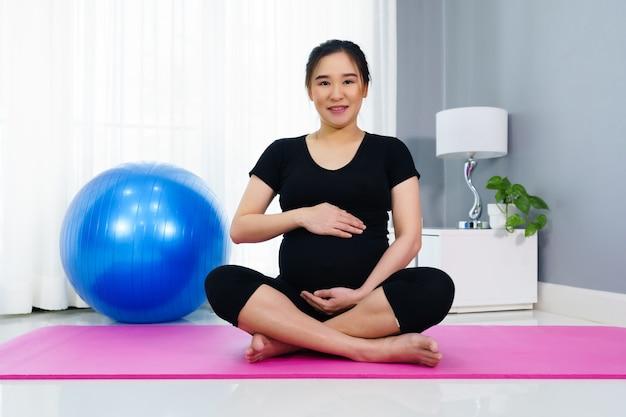 Donna incinta che fa esercizio di yoga nel soggiorno di casa