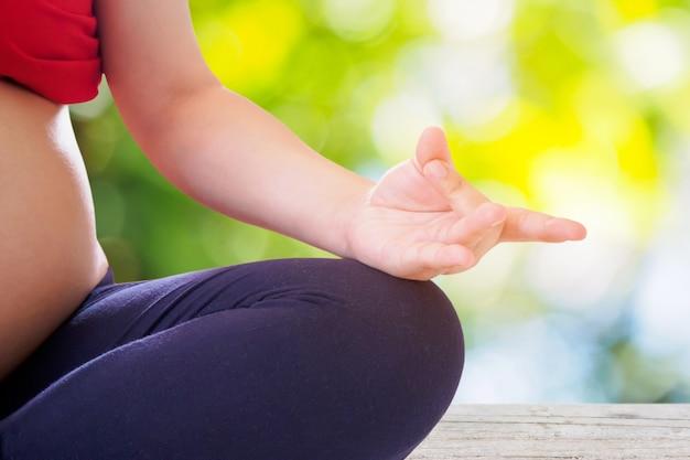 Donna incinta che fa yoga con la superficie del bokeh della natura Foto Premium