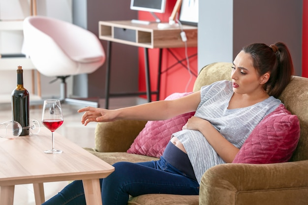 Donna incinta che beve alcolici a casa