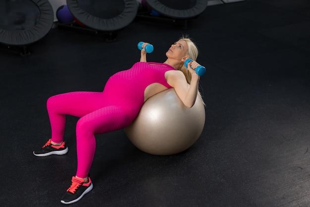 Donna incinta esercizio con manubri su bal fitness in palestra caucasica femminile allenamento fit palla gravidanza sport stile di vita sano concetto