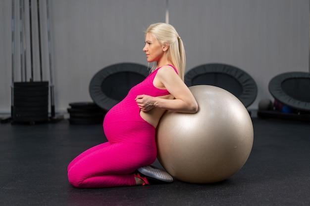 Donna incinta esercizio con fitness bal in palestra caucasica allenamento femminile fit ball gravidanza sport stile di vita sano concept