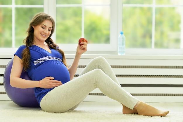 La donna incinta si esercita con la palla ginnica a casa