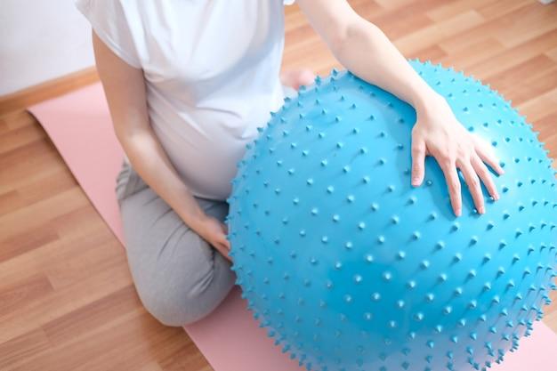 Una donna incinta fa sport con una palla fitness e yoga. concetto di cibo, stile di vita sano.