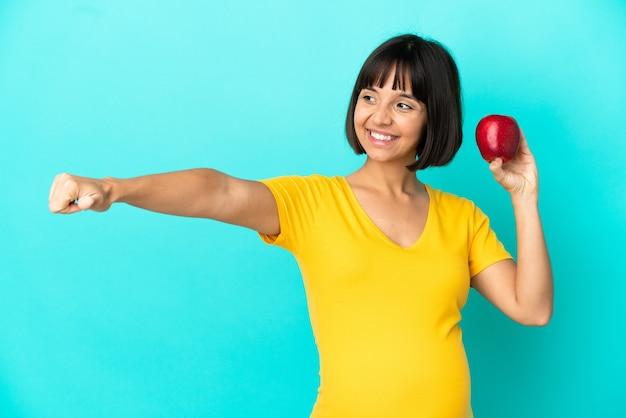 Donna incinta che tiene una mela isolata su fondo blu che dà un gesto di pollice in alto