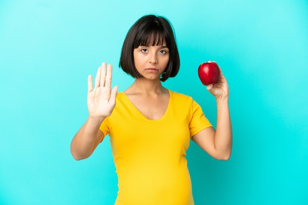 Donna incinta che tiene una mela isolata su fondo blu che fa gesto di arresto