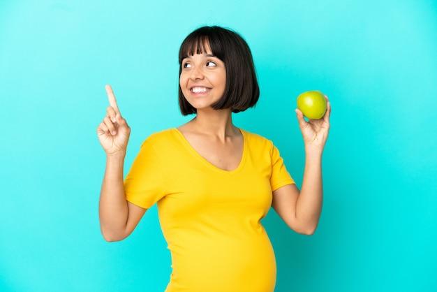 Donna incinta che tiene una mela isolata su fondo blu che indica una grande idea
