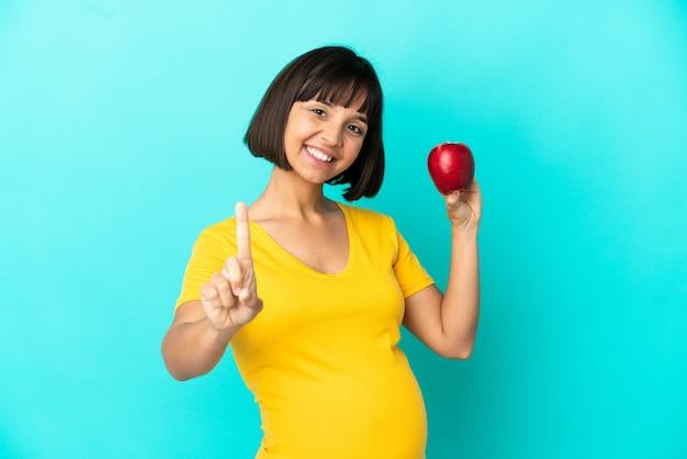 Donna incinta che tiene una mela isolata su sfondo blu che mostra e solleva un dito