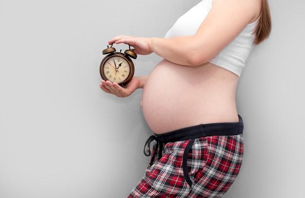 Orologio della holding della donna incinta