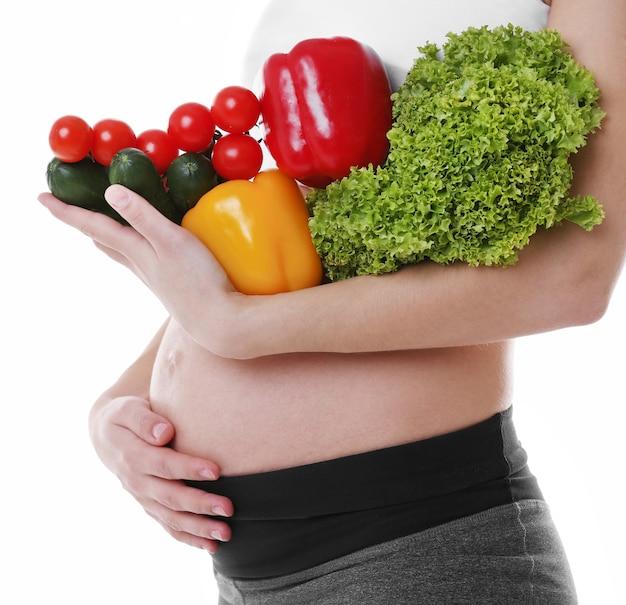 Donna incinta che tiene la verdura fresca, isolata su bianco