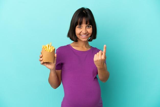 Donna incinta che tiene patatine fritte su sfondo isolato facendo gesto imminente