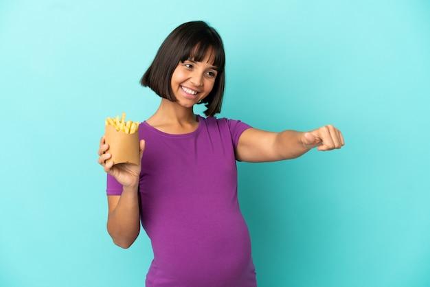 Donna incinta che tiene patatine fritte su sfondo isolato dando un gesto di pollice in alto