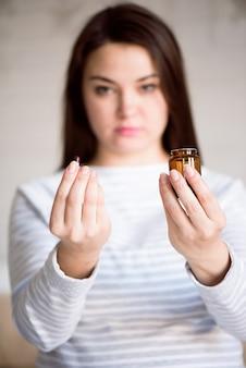 Medicina della holding della donna incinta. ragazza che tiene le pillole nelle sue mani.