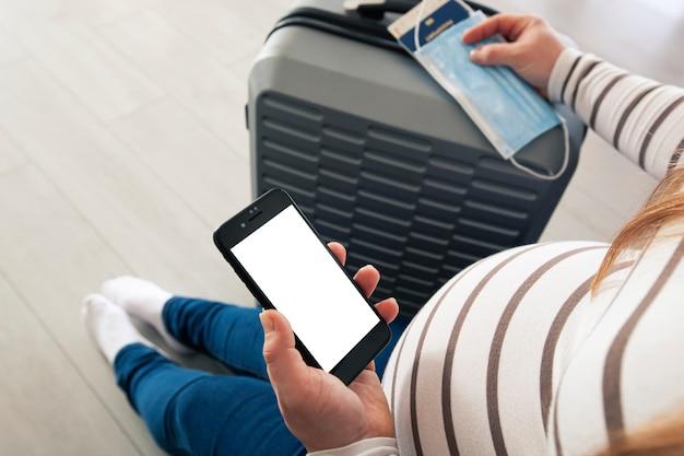 La donna incinta che tiene il telefono cellulare con schermo vuoto per certificato di vaccinazione digitale