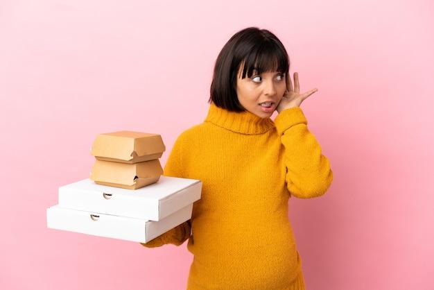Donna incinta che tiene pizze e hamburger isolati su sfondo rosa ascoltando qualcosa mettendo la mano sull'orecchio