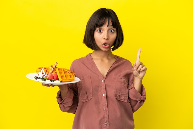Donna incinta che tiene i waffle isolati su sfondo giallo con l'intenzione di realizzare la soluzione mentre si solleva un dito