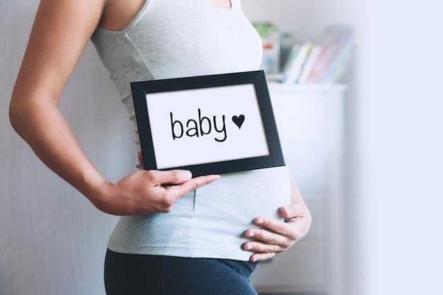 La donna incinta tiene la lavagna con il messaggio di testo baby gravidanza concept