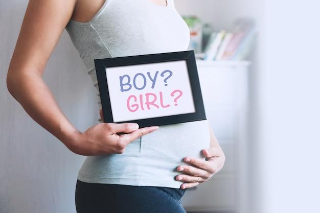La donna incinta tiene la lavagna con il messaggio di testo ragazzo o ragazza concetto di gravidanza