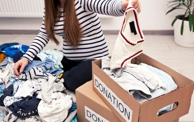 Una donna incinta sta smistando i vestiti per bambini e vuole dare alcune cose in beneficenza