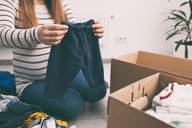 La donna incinta sta smistando i vestiti per bambini