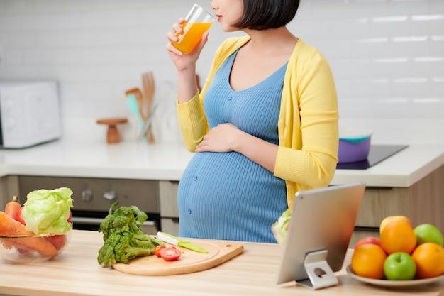 Donna incinta in cucina a bere succo di frutta sano