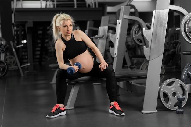 Donna incinta alzando i manubri allenamento bicipiti in palestra seduta panchina gravidanza, stile di vita sano, sport e concetto di fitness formazione di allenamento atleta femminile caucasico