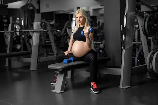 Donna incinta che solleva manubri allenamento muscolo bicipite in palestra seduta panchina gravidanza, stile di vita sano, sport e concetto di fitness allenamento allenamento atleta femminile caucasico
