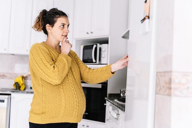 Donna incinta che osserva al frigorifero con l'espressione preoccupata