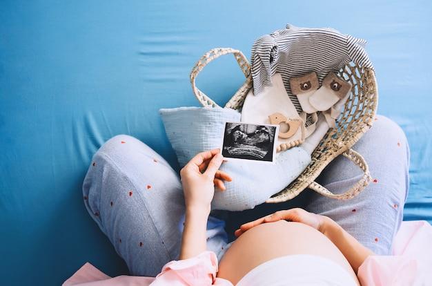 Donna incinta che guarda le immagini dell'ecografia durante la gravidanza