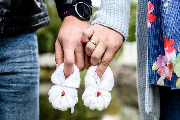 Donna incinta e marito amorevole che tengono le scarpette del bambino.