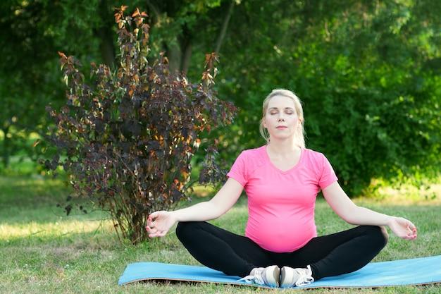 Donna incinta meditando all'aperto, natura paesaggio. signora gravida che pratica yoga, mantenendo la calma. prepararsi per il travaglio