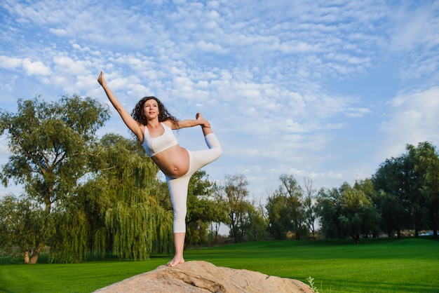 Donna incinta nella posa di meditazione sulla pietra