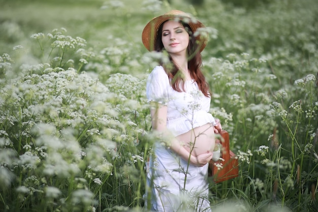 Donna incinta in natura per una passeggiata in estate