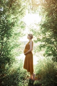 Donna incinta in tempo caldo del parco all'aperto