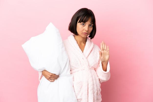 Donna incinta in pigiama isolato su sfondo rosa facendo gesto di arresto