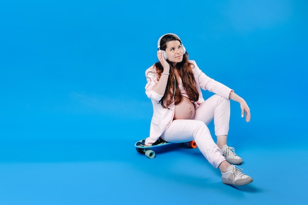 Una donna incinta con un abito rosa si siede su uno skateboard con le cuffie e ascolta musica su sfondo blu.